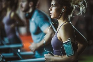 Determined athletic woman listening music while jogging on treadmill in a gym.